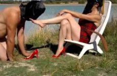 De meesteres laat in de buitenlucht haar voeten likken